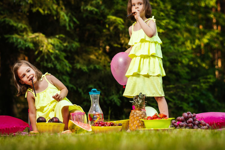 Picnic Girl Child Childhood Kid Forest Summer Sister Sisters Twins Women Food And Drink Girls Container Plant Females Food Nature Grass Day Front View Real People Leisure Activity Togetherness Lifestyles Two People Family Outdoors Innocence