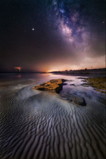 Scenic view of sea against sky and milkyway at night