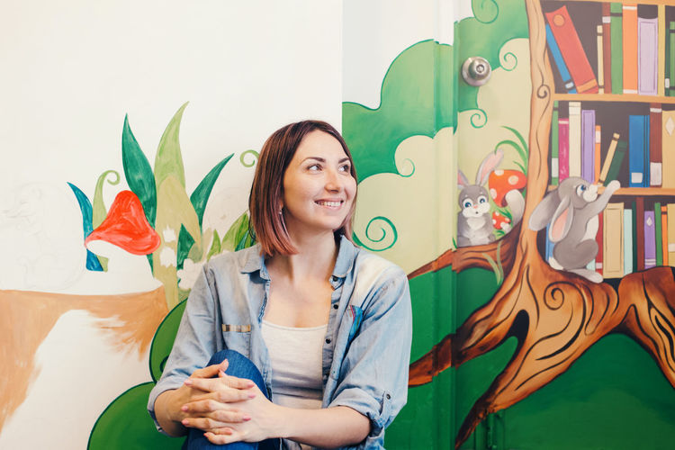 Smiling woman sitting against painted wall