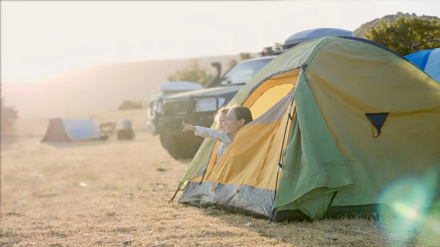 Rear view of woman standing in tent on field