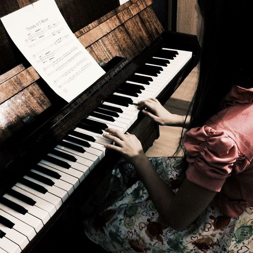 High Angle View Of Woman Playing Piano
