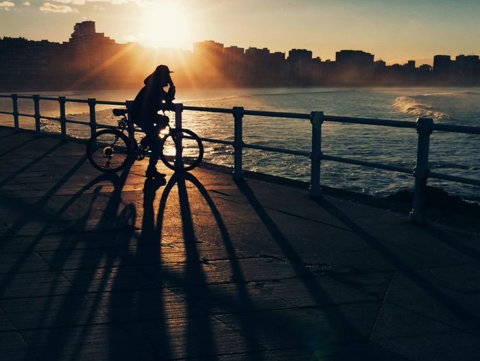 Silhouette person riding bicycle on promenade against sky during sunset