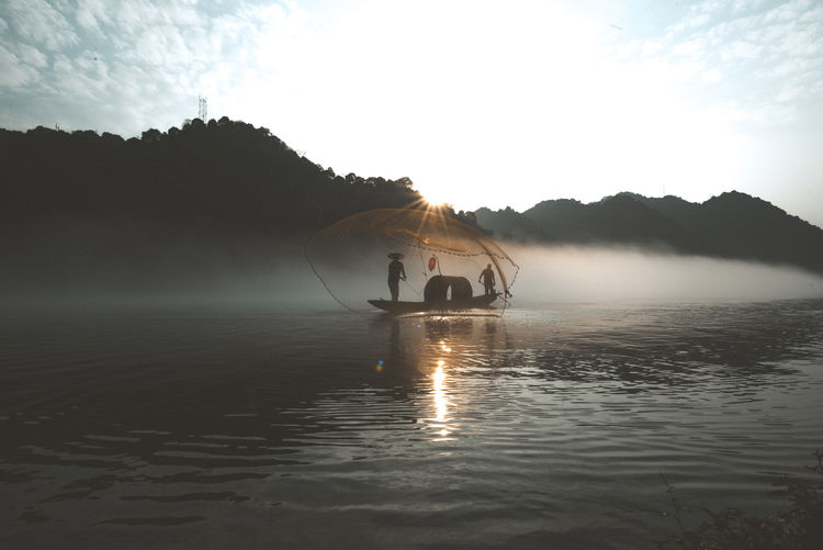 People in fishing boat on lake against sky