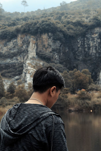 Rear view of man standing by lake against mountain