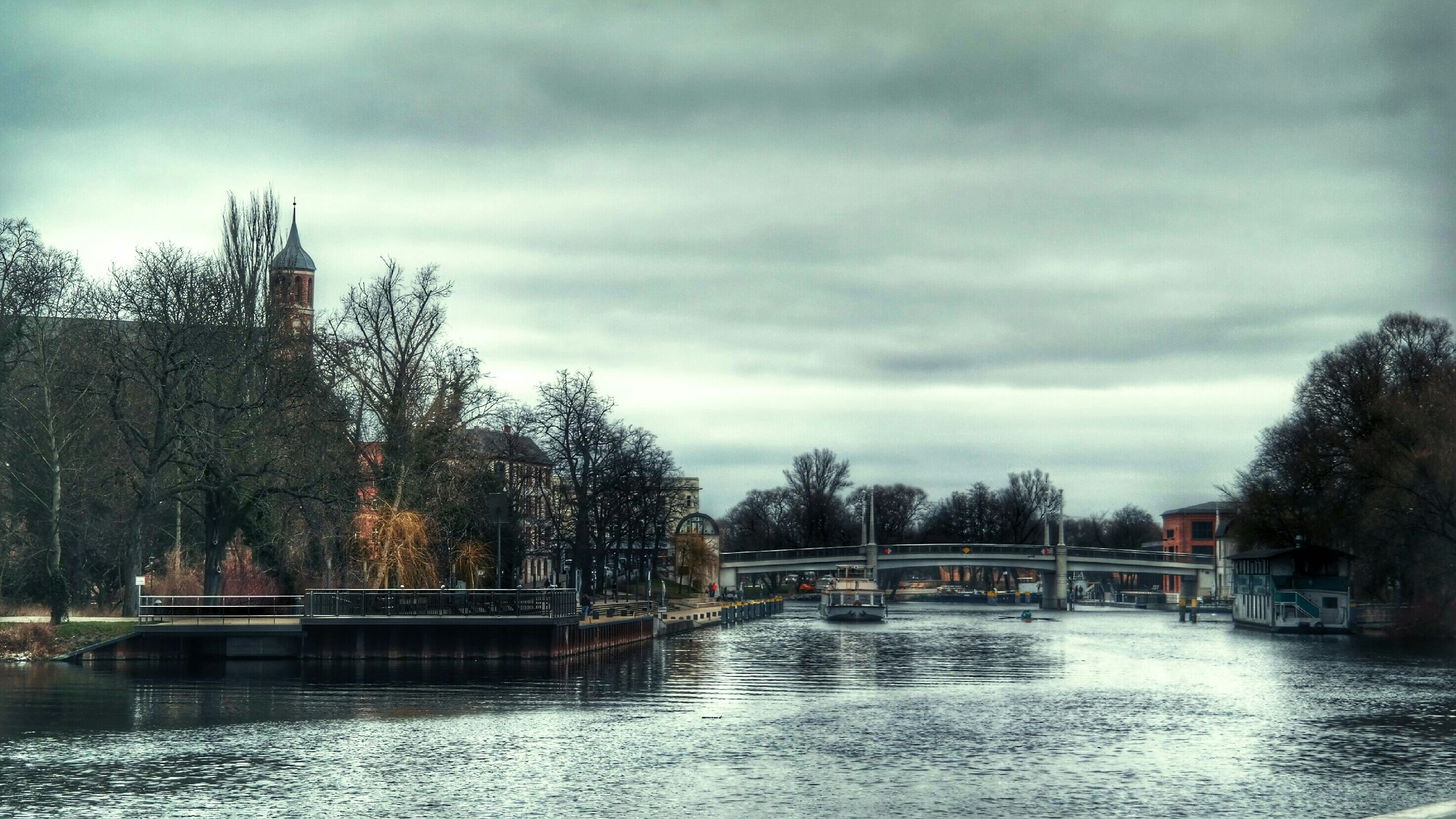 sky, tree, cloud - sky, water, cloudy, built structure, waterfront, architecture, cloud, river, weather, overcast, nature, lake, tranquility, building exterior, tranquil scene, beauty in nature, scenics, bridge - man made structure