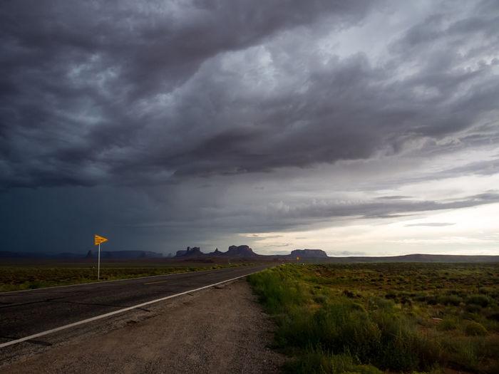 Road passing through landscape against storm clouds