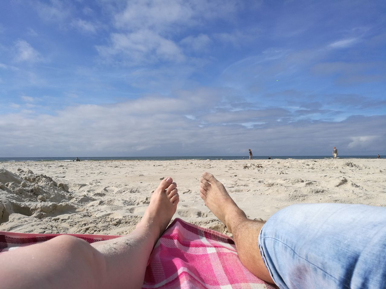 Low Section Of People Relaxing At Beach Against Sky