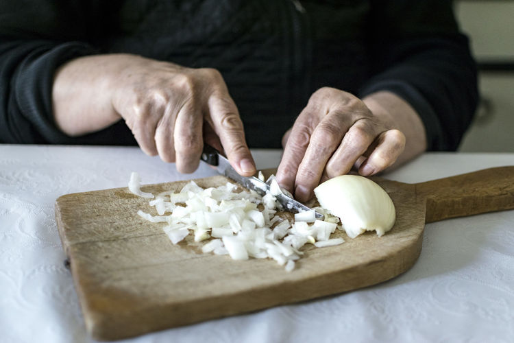 Cropped Hand Of Person Preparing Food On Cutting Board