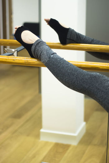 Low section of woman exercising by mirror in gym