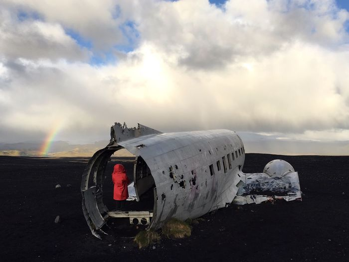 Rear View Of Woman Standing In Crashed Airplane On Field Against Cloudy Sky