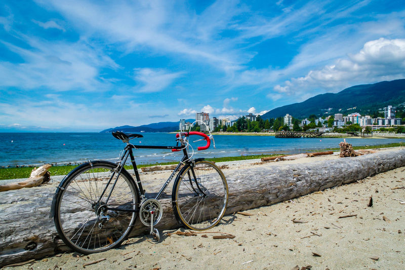 Bicycle parked at beach against cloudy sky