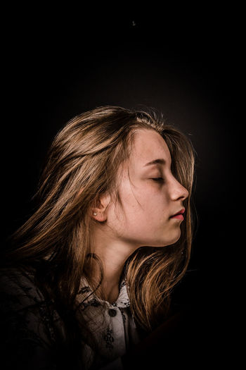 Portrait of a serious young woman over black background