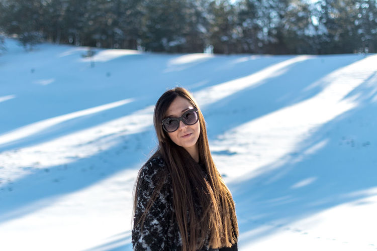 Cold Temperature Winter Snow Glasses Leisure Activity One Person Portrait Lifestyles Real People Looking At Camera Smiling Nature Sunlight Day Long Hair Young Women Young Adult Sunglasses Hairstyle Hair Fashion Outdoors Warm Clothing