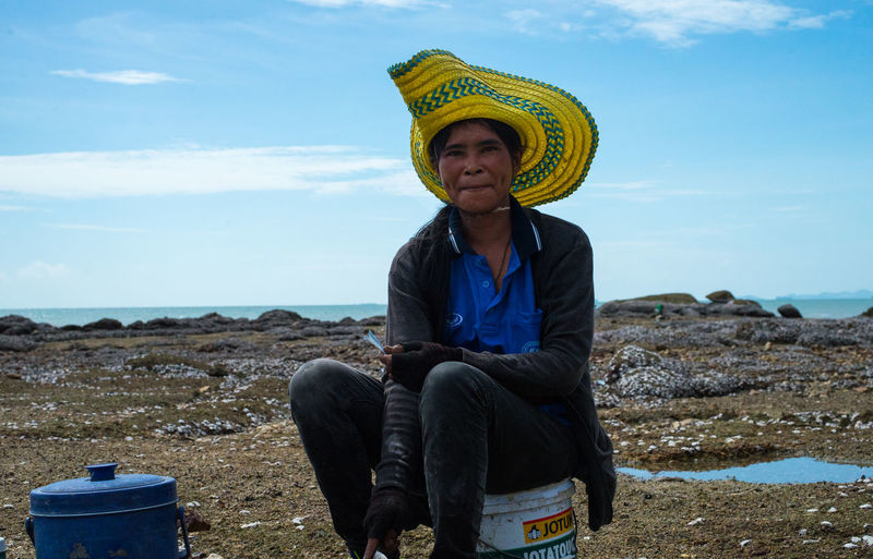 Portrait of woman standing against blue sky