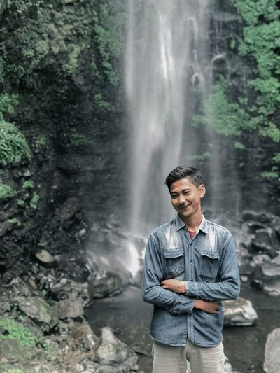 Portrait of young man standing against waterfall in forest