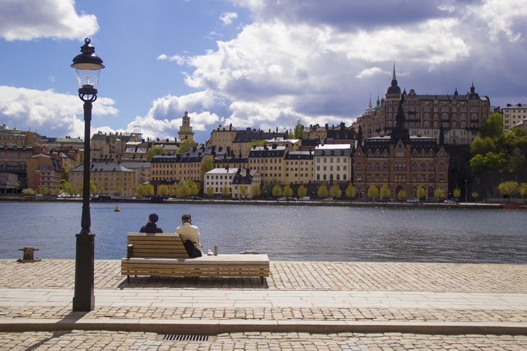 People sitting on bench by river against buildings in city