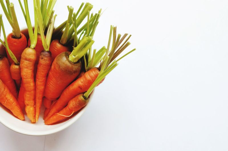 Close-up of vegetables in plate against white background