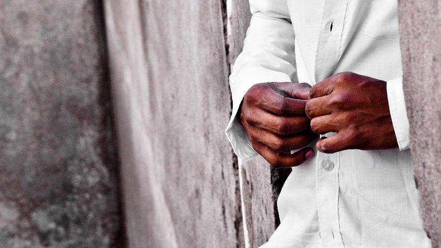 Close-up of man buttoning shirt