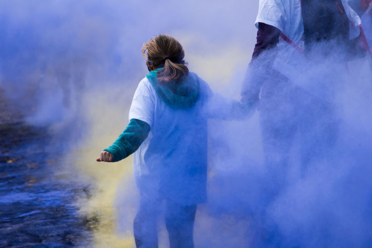 Rear view of mother and daughter standing amidst powder paint during holi