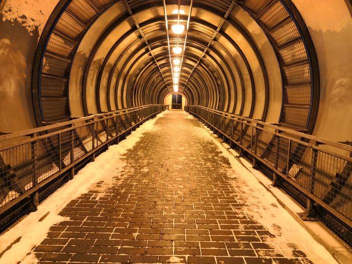Empty footpath in illuminated tunnel
