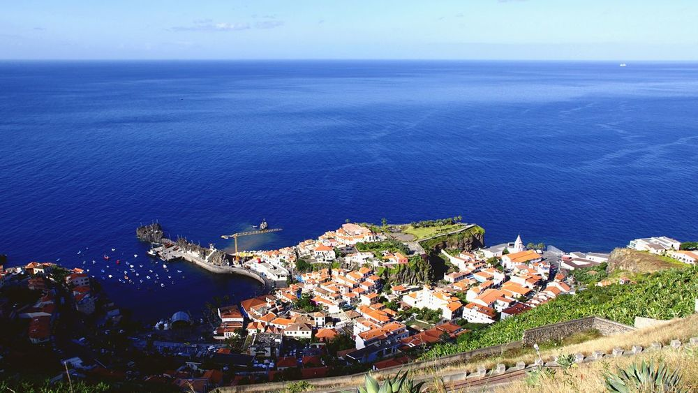 View over Camara de Lobos, Madeira. Sea Building Exterior High Angle View Architecture Built Structure Day House Horizon Over Water Water Outdoors Blue Town No People Scenics Cityscape Aerial View Sky