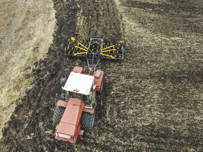 Aerial view of a modern tractor plowing dry field, preparing land for sowing Aerial Agriculture Field Tractor Farm Ground Soil Countryside Combine Machinery Motion Working Plowing High Angle View Transportation Outdoors Mode Of Transportation Industry Land Vehicle Land Nature Landscape