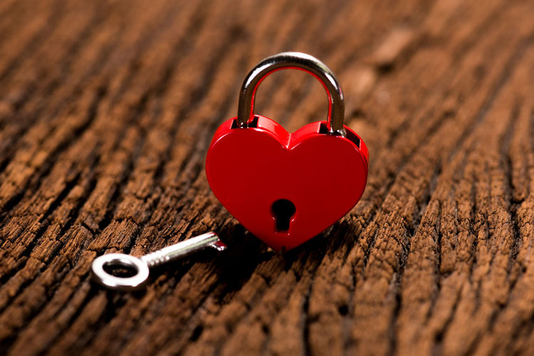 Close-up of red heart shape padlock on table