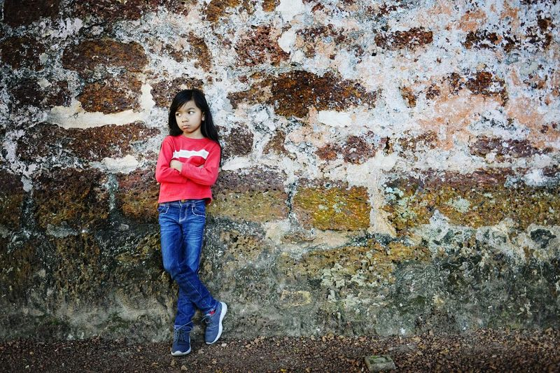 Full length of girl with arms crossed standing against wall