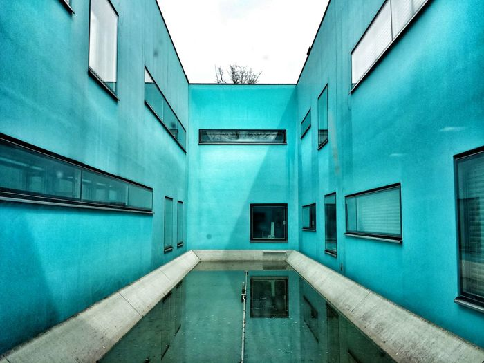 Pond Amidst Turquoise Building