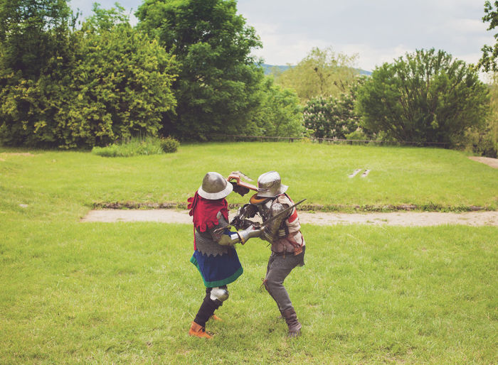 Two people in period costume fighting on field