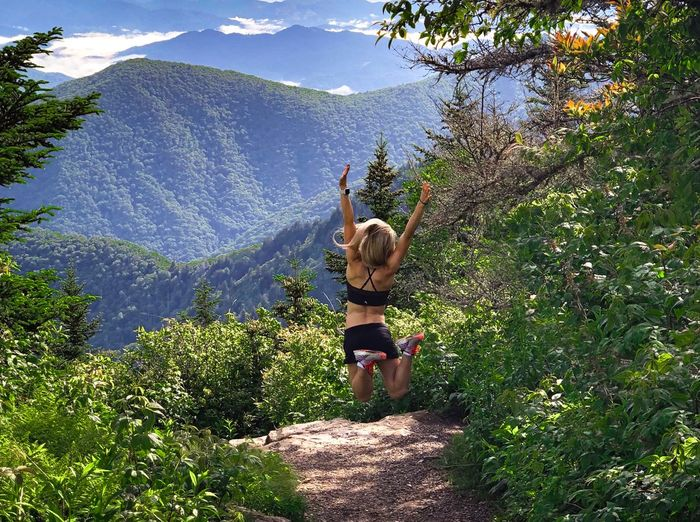 We made it Fitness Outdoor Photography Mountain Range Success Happiness Expression Excitement Jump Plant One Person Tree Real People Leisure Activity Nature Day Green Color Beauty In Nature Full Length Sunlight Casual Clothing Growth Lifestyles Water Childhood Standing Rear View Arms Raised Child