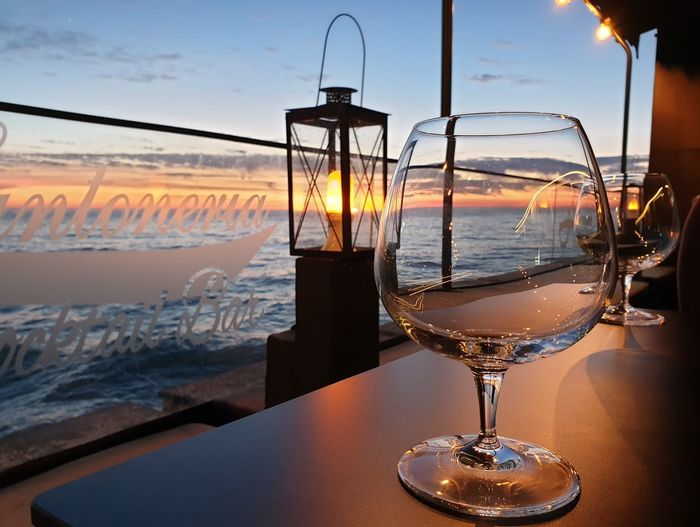 Close-up of wine glass on table against sea during sunset