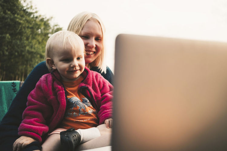 Rear view of smiling girl sitting on laptop