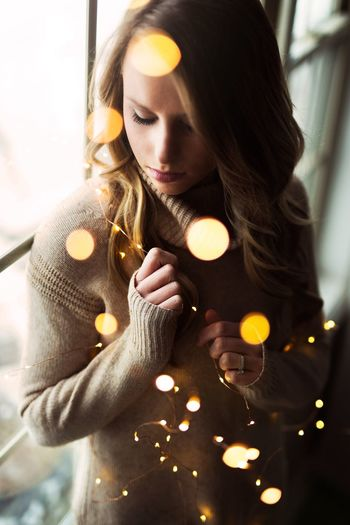 Beautiful woman amidst magical bokeh lights. One Person Young Adult Real People Indoors  Young Women Looking Down Holding Home Interior One Young Woman Only Lifestyles Day Close-up People Window Beautiful Woman Women Bokeh Bokeh Photography Christmas Lights Magical Portrait