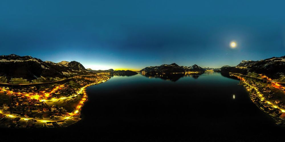 Scenic view of lake and illuminated landscape against clear sky at night