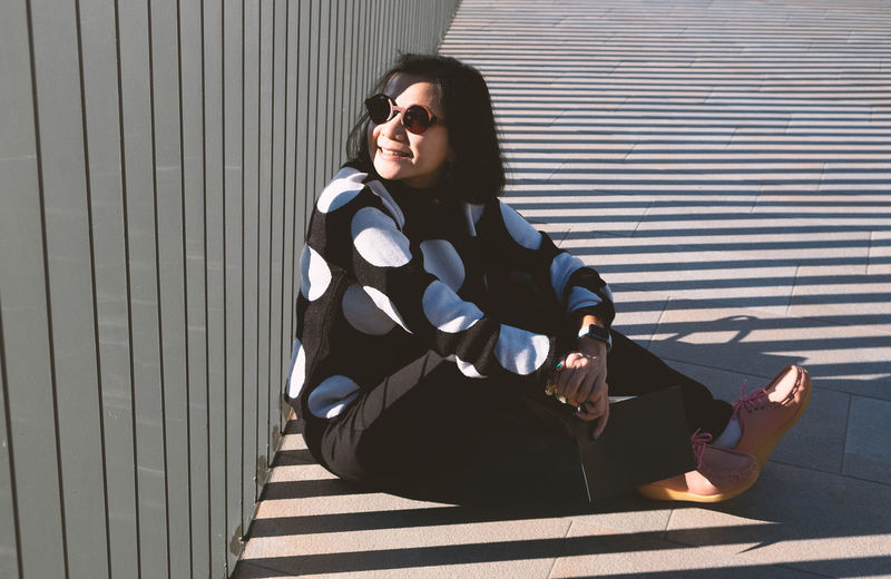 Side view of woman wearing sunglasses sitting on footpath