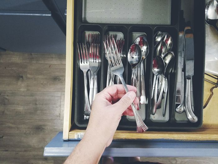 Cropped hand holding fork above drawer in kitchen