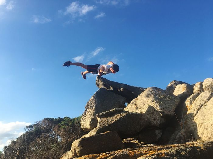 Low angle view of man balancing on rock against sky