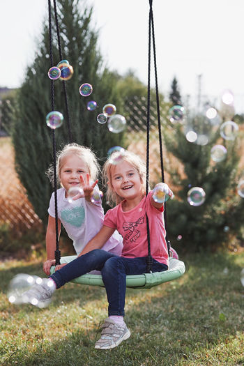 Portrait of smiling siblings gesturing towards bubbles while sitting on swing