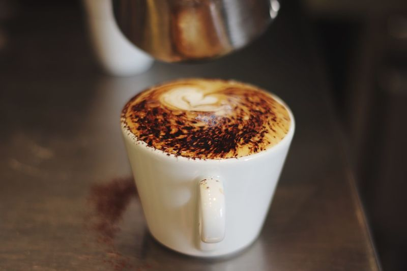 Coffee with milk and cacao in top EyeEm Selects Coffee - Drink Coffee Cup Drink Food And Drink Refreshment EyeEmNewHere Cup Cappuccino Frothy Drink Close-up Saucer Focus On Foreground Table No People Brown Indoors  Latte Freshness Mocha Froth Art Food