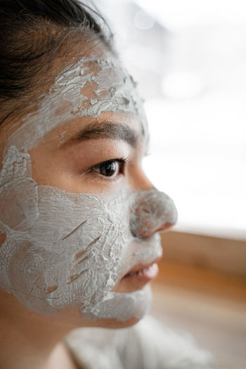 Close-up of woman with facial mask looking away