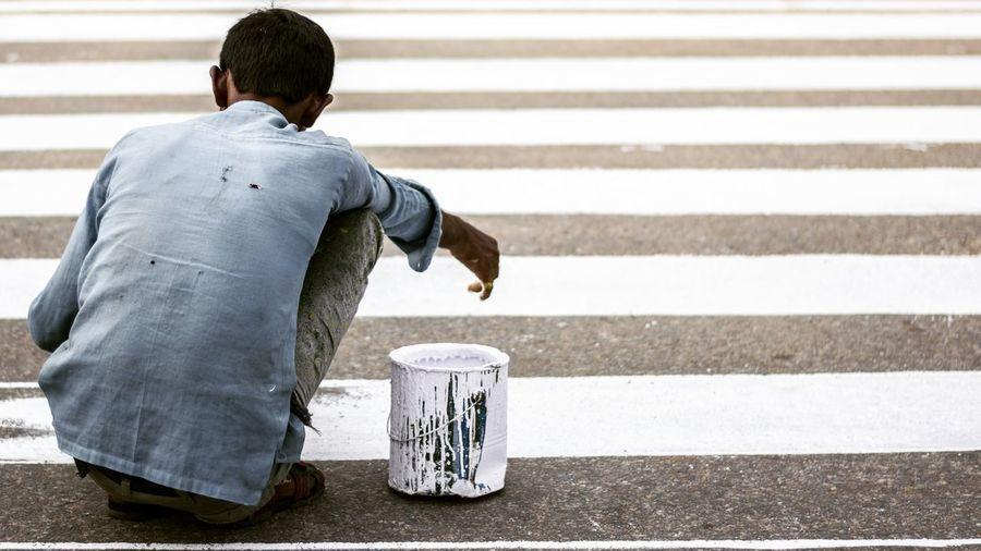Rear View Of Worker Making Zebra Crossing On Road
