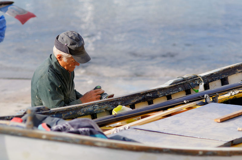 Man working on boat against sea