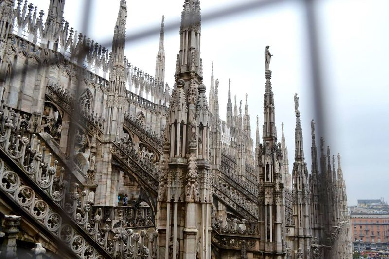 Low angle view of milan cathedral seen through metal grate