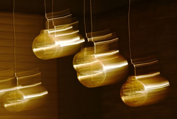 Blurred motion of illuminated light bulbs hanging