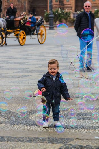 The innocence Rainbow Outdoors Fun Playing Smiling Happiness Multi Colored Bubble Children Only Childhood Bubble Wand Child Be. Ready. Future Enjoying Life Streetphotography Stories From The City