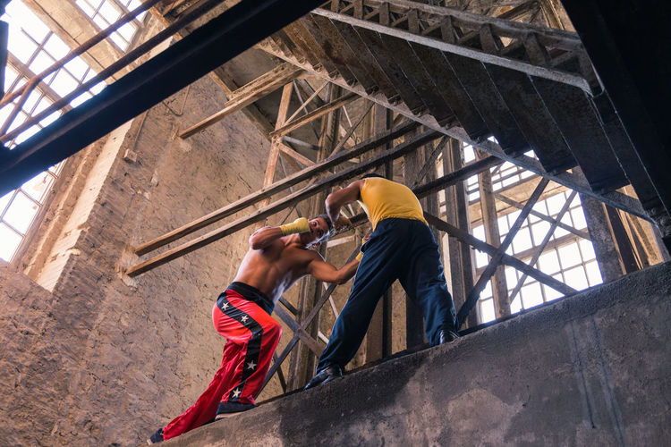 Low angle view of men boxing at construction site