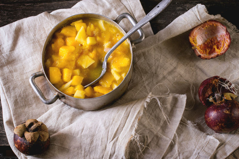 Making mango chutney or jam in vintage aluminum pan over old table with empty glass jar, mango and mangosteen. Aluminum Chutney Fruit High Angle View Homemade Homemade Food Jam Kitchen Making Mango Mangosteen Pan Passion Fruit Rustic Spoon Sweet Sweet Food Utensil Vintage Yellow
