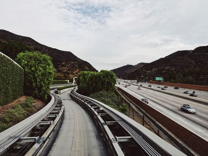 Tram Tracks By Highway Against Sky