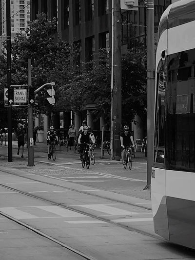 People riding bicycle on street against buildings in city